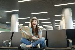 Young laughing traveler tourist woman with crossed legs hold paper map, search route waiting in lobby hall at. International airport. Passenger traveling abroad stock photo