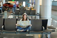 Young laughing traveler tourist woman with crossed legs hold paper map, search route, waiting in lobby hall at. International airport. Passenger traveling stock images