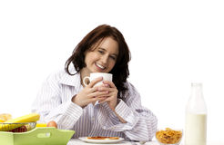 Young laughing woman at breakfast. Young laughing woman holding coffee mug at breakfast Stock Image