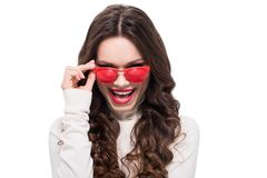 Young laughing woman with bright makeup looking over her red sunglasses,. Isolated on white stock photography