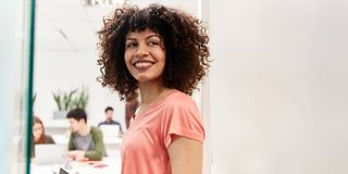 Young laughing woman in co-working space royalty free stock images