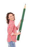 Young laughing woman with huge green pencil Stock Photography