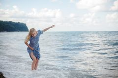 Young smiling woman in a long dress. Young laughing woman in long dress in the sea is in raptures from waves Stock Photos