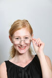 Young laughing woman looks over his glasses Royalty Free Stock Images