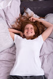 Young laughing woman lying on her bed at home Royalty Free Stock Image