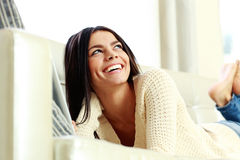 Young laughing woman lying on the sofa Stock Photos