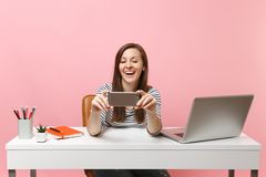Young laughing woman making video call doing taking selfie shot on mobile phone while sit work at white desk with pc royalty free stock images