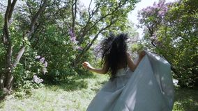 Young laughing woman with red apple running through sunny garden, slow motion. Beautiful brunette in blue dress is running through a garden, holding red apple in stock video footage