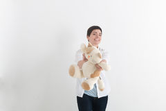 Young laughing woman with short hair in casual style giving forward plush toy cat and looking at camera with tooth smile royalty free stock photography