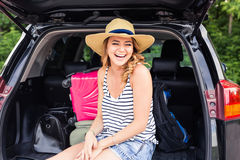 Young laughing woman sitting in the open trunk of a car. Summer road trip Stock Photography