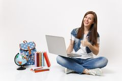 Young laughing woman student hold using laptop pc computer showing thumb up sitting near globe backpack, school books. Isolated on white background. Education stock photos