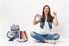 Young laughing woman student pointing index finger up holding alarm clock sitting near globe, backpack, school books royalty free stock photo