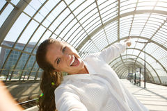 Young laughing woman taking selfie and pointing Stock Images