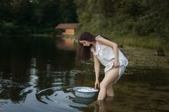 Young laundress stands in the river royalty free stock photography