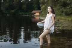 Young laundress stands in a river and holds a basin in her hands stock photo
