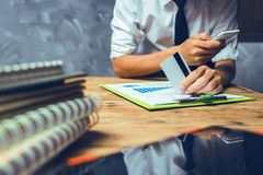 Young lawyer business man working hard top help his customer wit. H messy paperwork on the old grunge wooden desk in loft style office workplace Stock Image