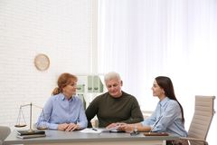 Young lawyer consulting senior couple. In office stock photography