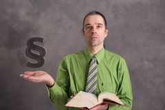 Young lawyer in green shirt with statute book and paragraph. Young lawyer in green shirt and necktie with statute book and paragraph Royalty Free Stock Photo