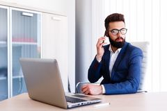 Young Lawyer Talking On Phone While Works On Laptop. Young Business Man Working On Laptop At Office - Workplace Stock Photo