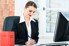 Lawyer in office making notes in a file. Young lawyer working in her Office, she is sitting behind folders writing into a file stock image