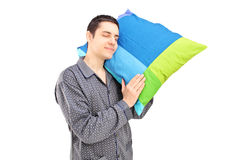 A young lazy guy holding a pillow and sleeping Stock Images