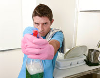 Young lazy house cleaner man washing and cleaning the kitchen with detergent spray bottle. And sponge in stress aiming as with a gun in male housework and royalty free stock image