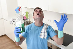 Young lazy house cleaner man washing and cleaning the kitchen with detergent spray bottle. And sponge in stress and desperate face expression in male housework stock images