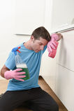 Young lazy house cleaner man washing and cleaning the kitchen with detergent spray bottle. And sponge in stress and desperate face expression in male housework stock photo