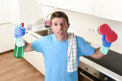 Young lazy house cleaner man washing and cleaning the kitchen with detergent spray bottle. And sponge in stress and desperate face expression in male housework stock photos
