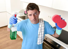 Young lazy house cleaner man washing and cleaning the kitchen with detergent spray bottle. And sponge in stress and desperate face expression in male housework royalty free stock image