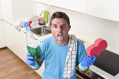 Young lazy house cleaner man washing and cleaning the kitchen with detergent spray bottle. And sponge in stress and desperate face expression in male housework royalty free stock photography