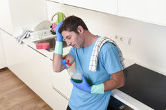 Young lazy house cleaner man washing and cleaning the kitchen with detergent spray bottle Stock Images