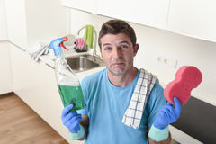Young lazy house cleaner man washing and cleaning the kitchen with detergent spray bottle. And sponge in stress and desperate face expression in male housework stock photography