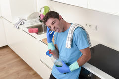Young lazy house cleaner man washing and cleaning the kitchen with detergent spray bottle. And sponge in stress and desperate face expression in male housework stock image