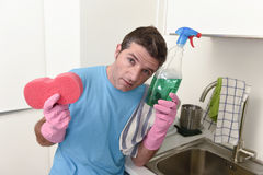 Young lazy house cleaner man washing and cleaning the kitchen tired in stress. Young lazy house cleaner man washing and cleaning the kitchen with detergent spray Royalty Free Stock Image