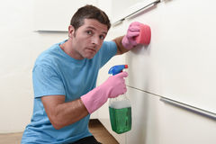 Young lazy house cleaner man washing and cleaning the kitchen tired in stress Royalty Free Stock Photo
