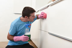 Young lazy house cleaner man washing and cleaning the kitchen tired in stress. Young lazy house cleaner man washing and cleaning the kitchen with detergent spray stock photography