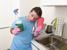 Young lazy house cleaner man washing and cleaning the kitchen wi. Th detergent spray bottle and sponge in stress and desperate face expression in male housework stock photography