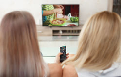Young lazy housewives watching cooking channel in TV Stock Photo