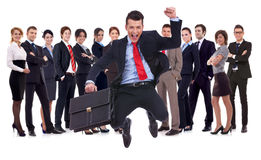 Young leader jumping for joy in front of his team royalty free stock images