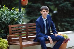 A young lean guy, the student is sitting on a bench in the park, today he is a jeweler and very happy. The groom wears a. Classic shadow suit and a blue tie royalty free stock photo