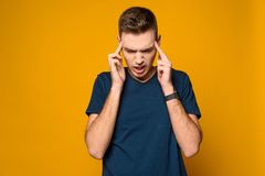 Young lean guy tries to remember something. Isolated on yellow background. Studio portrait. Male emotions stock image