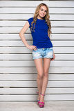 Young leggy blond woman. In jeans shorts and blue t-shirt posing near the white wooden wall Royalty Free Stock Photos