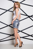 Young leggy blonde. Posing in shorts and top Royalty Free Stock Photo
