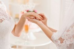 Young lesbian bride putting ring on finger. Of her future wife Royalty Free Stock Images