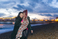 Young lesbian couple enjoying a night out. Young couple of lesbian girls enjoying a night out at the seaside laughing and smiling as they hug each other on the Stock Photos