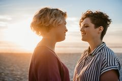 Young lesbian couple enjoying a romantic beach sunset together royalty free stock photography