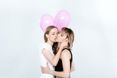 Young lesbian couple holding pink balloons and kissing. Beautiful young lesbian couple holding pink balloons and kissing Royalty Free Stock Images