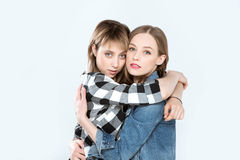 Young lesbian couple hugging and posing together isolated on blue Royalty Free Stock Image