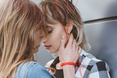 Young lesbian couple kissing with eyes closed outdoors. Close up portrait of young lesbian couple kissing with eyes closed outdoors Stock Images